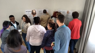 Workshop attendees scribbling on wall posters as an activity